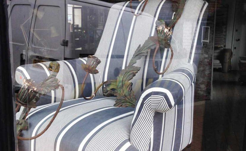 イギリスのアンティークショップのウインドウにティッキンギリネンで張った椅子が飾られていました。